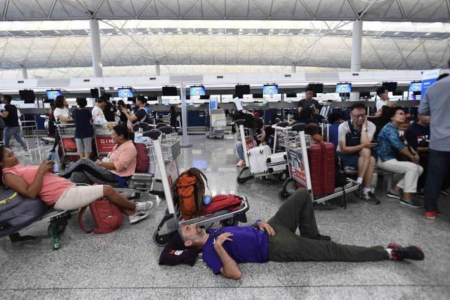 香港大批反送中示威者以機場手推車等堵塞香港國際機場1號客運大樓旅客登機。(中新社)