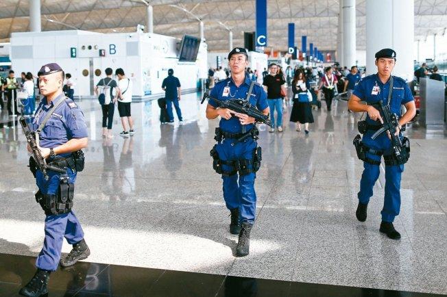 香港警察8月14日荷槍實彈在機場出境大廳巡邏。 (聯合新聞網)