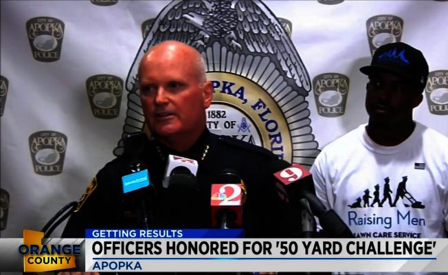阿波卡警察局長Michael McKinley宣布該警局已完成挑戰50的一半。右為發起人Rodney Smith。(截自視頻)