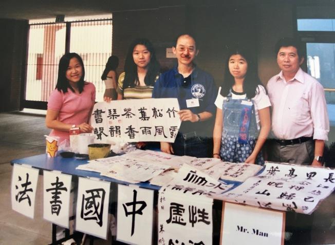聖蓋博高中華人教師文華東(中)和學生在校園節日展示中國書法習作。(本報檔案照)