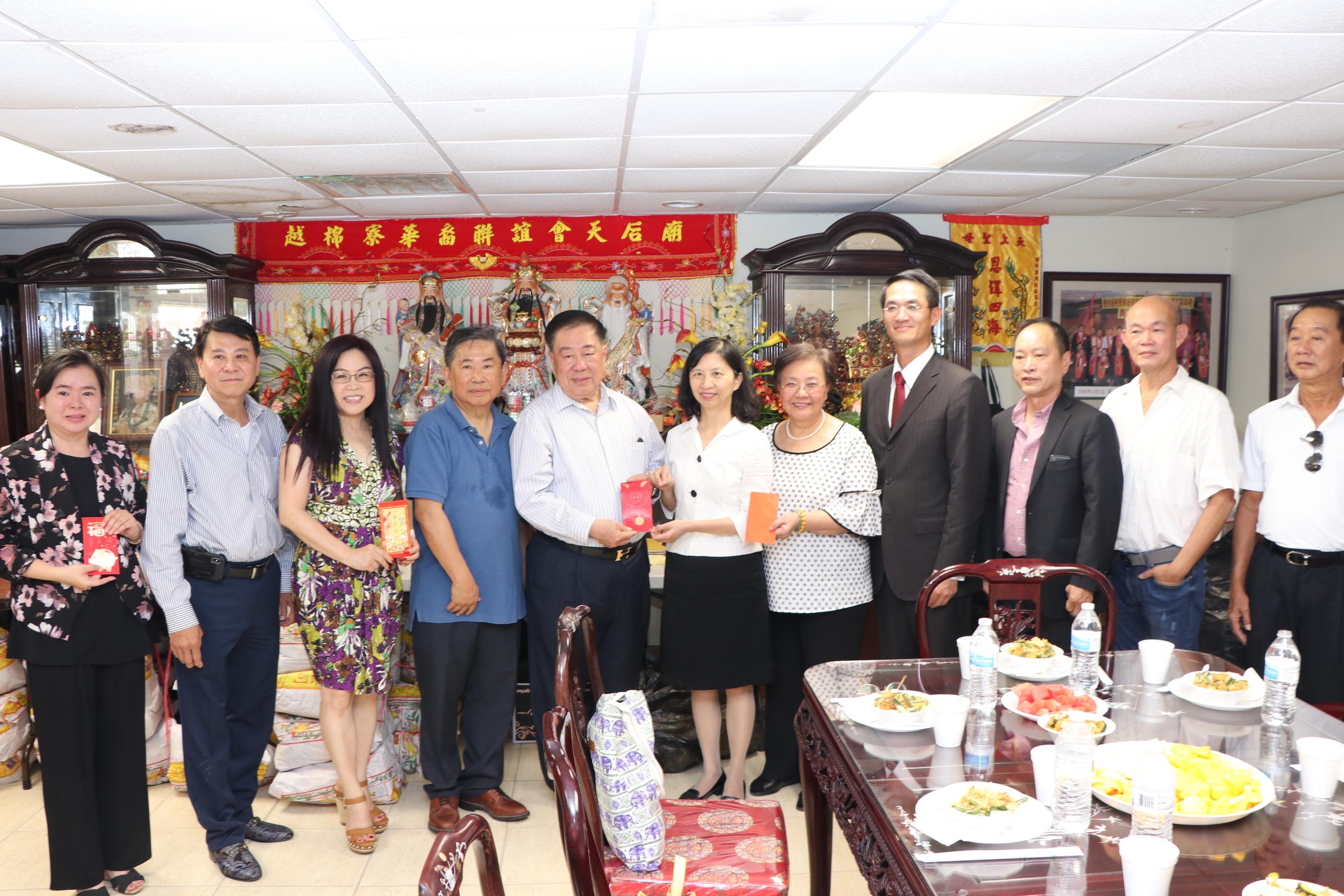 周滿洪(左五)代表天后廟接受陳家彥(右四)等捐贈的香油錢。