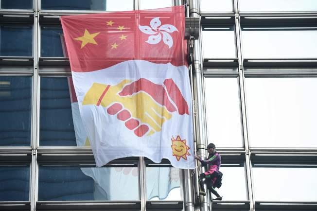 外號「法國蜘蛛人」的羅貝爾,昨爬上李嘉誠的長江集團中心大廈,掛上巨型布條,上面印有大陸五星旗和香港區徽,以及兩隻手握手的圖樣,呼籲港府和示威民眾協商。(Grtty Images)