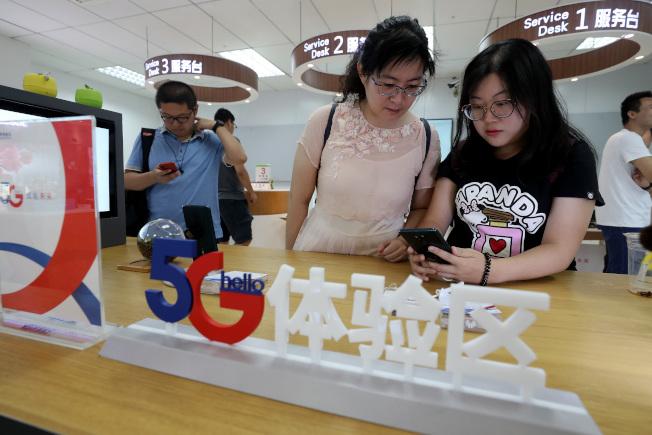 華為首款5G商用手機16日全中國開售,消費者在北京的中國電信營業廳體驗5G手機。 (中新社)