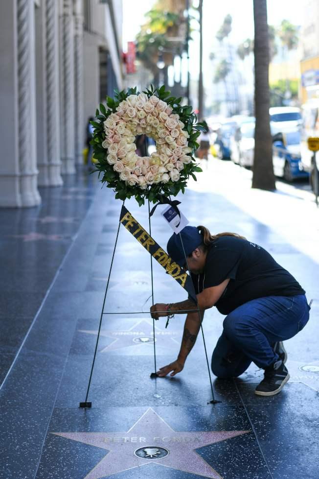 資深演員彼得方達16日病逝洛杉磯家中,享年79歲;噩耗傳出後,影迷在立著花圈的好萊塢星光大道他的名字前拍照悼念。(Getty Images)