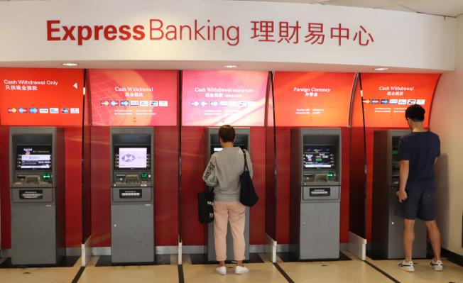 香港「反送中」支持者呼籲透過在提款機提款來攻擊金融體系和銀行,但本地銀行的提款機16日看來未受影響。圖為匯豐銀行灣仔分行的自動提款機。(中央社)