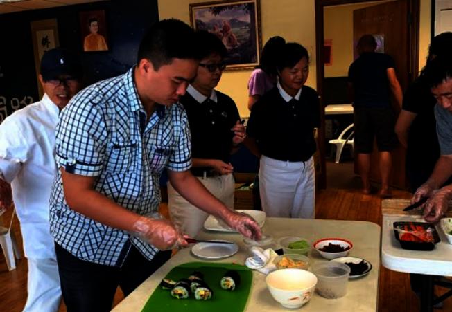 慈濟邁阿密慶祝吉祥月,舉辦包壽司素食活動,小青年學包壽司。(Judy Su提供)