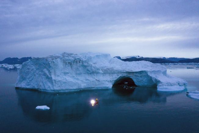 格陵蘭近北極,天寒地凍,圖中浮在海上的冰山,體積巨大。(美聯社)