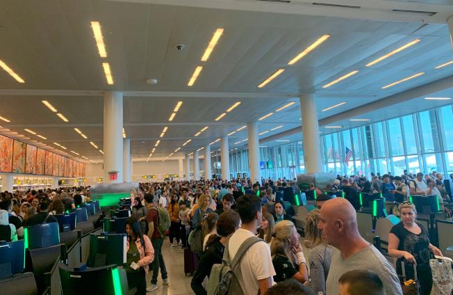全美海關電腦當機,各地機場大亂。圖為旅客在紐約甘迺迪機場大廳苦候。(美聯社)