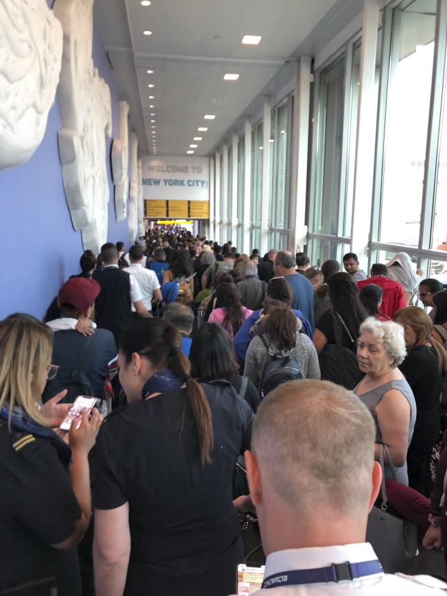 全美海關電腦當機,各地機場大亂。圖為抵達甘迺迪機場的旅客在走廊等候進關。(美聯社)