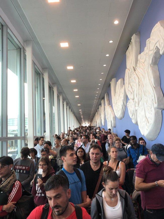 全美海關電腦當機,各地機場大亂。圖為旅客在紐約甘迺迪機場走廊苦候。(推特)