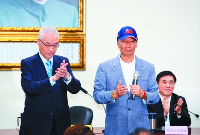 民黨副主席郝龍斌(右)當面向鴻海創辦人郭台銘表達安排與黨主席吳敦義(左)會面的「吳郭會」,盼能促成黨內團結;圖為郭先前獲頒榮譽黨證的畫面。(本報資料照片)