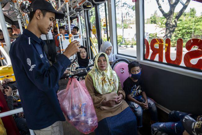 公車車掌在車上收集乘客的塑膠垃圾。(法新社)