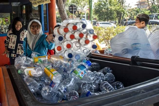 通勤者在公車總站拿塑膠瓶換車票。(法新社)