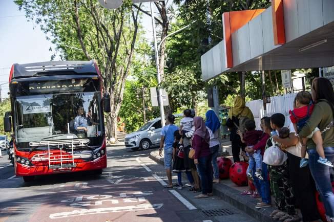 印尼泗水民眾排隊拿可回收的塑膠垃圾換公車票。(法新社)