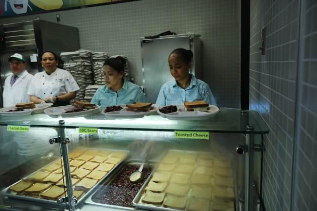 新州一個學區對欠繳午餐費的學童,不讓他們吃餐廳的熱食,改提供鮪魚三明治和全麥麵包。圖為紐約一所公校的學生餐廳工作人員正準備午餐。(Getty Images)