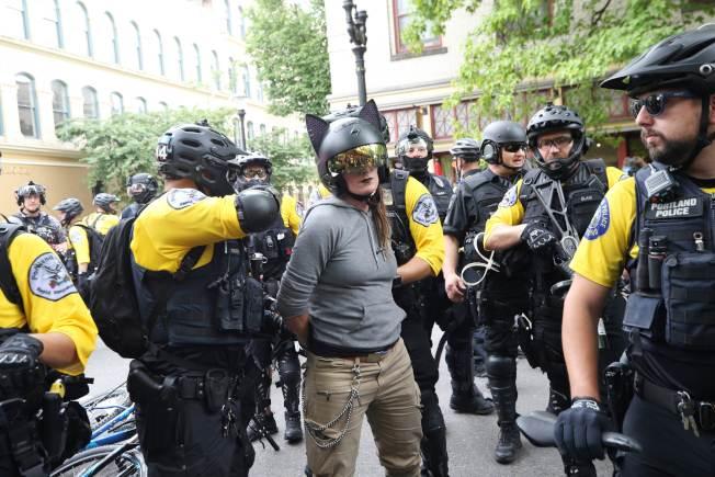 一名女子因為對著極右團體遊行隊伍加大摩托車油門排放廢氣,而被警方逮捕。(Getty Images)