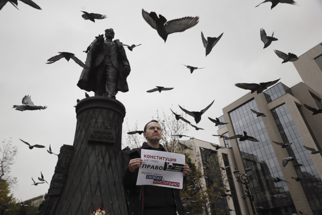一名示威者17日響應「一人抗爭」活動,手持寫著「當局踐踏憲法/將自由和憲法還給人民」 海報,在莫斯科市中心抗議。(美聯社)