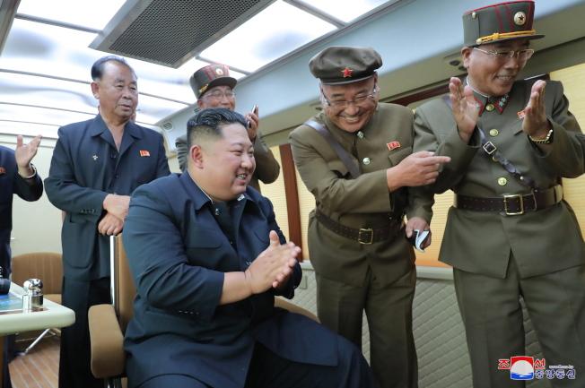 金正恩16日觀看試射過程,與北韓官員拍手慶祝試射成功。(歐新社)