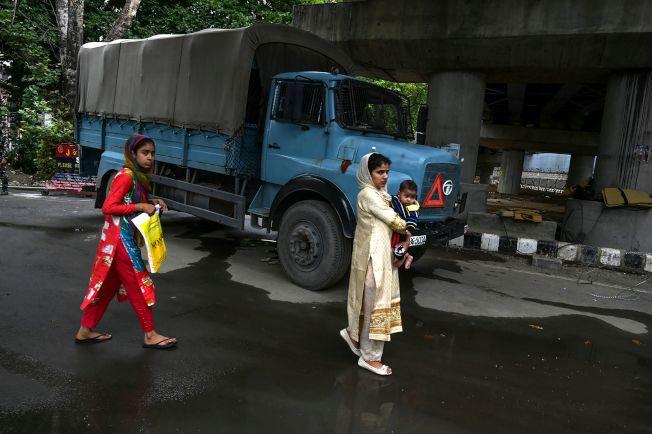 印度放鬆對喀什米爾管制,於17日恢復約100台電話交換機中17台機器營運。圖為喀什米爾行人於17日行經一輛安全部隊用車。(Getty Images)