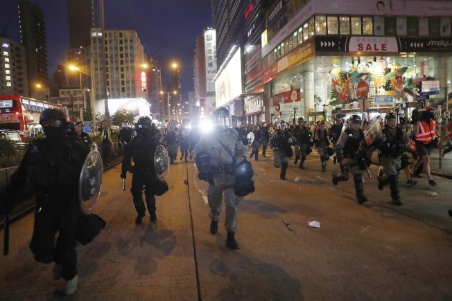 香港市民發起網上問卷調查顯示,自認「和平、理性、非暴力」的示威者,有98%認為警方沒有公正執法,圖為大批港警17日晚湧進旺角鬧區強制驅離示威者。(歐新社)