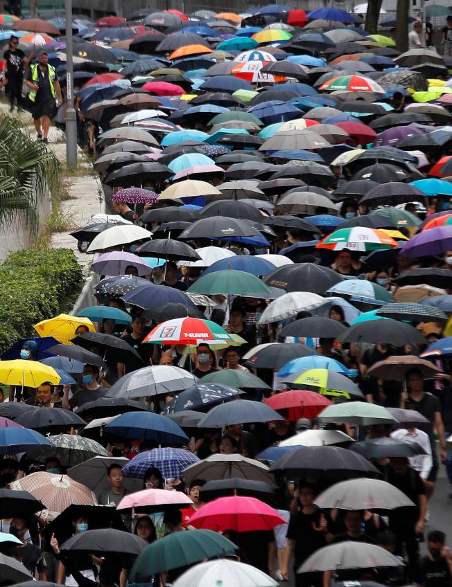 香港市民發起「收復紅土」(紅磡、土瓜灣)活動,成千上萬人撐著雨傘上街遊行。(路透)