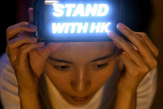 支持民主的香港市民在頭上舉起照明裝置,寫著「堅守香港」。(Getty Images)