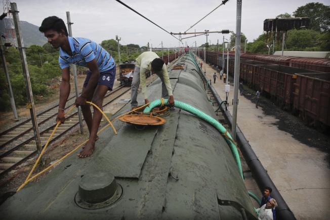 從喬拉爾佩特到清奈,每日都有「水罐列車」將250萬公升的水,送往應急。圖為工作人員將來自高韋里河與梅圖爾大壩的水,灌入車廂。 (美聯社)