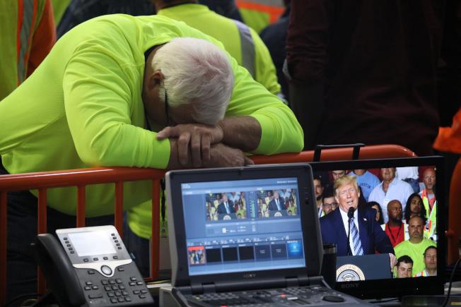 川普訪問賓州殼牌石油園區發表演說時,一名工人趴在欄杆上休息。(路透)