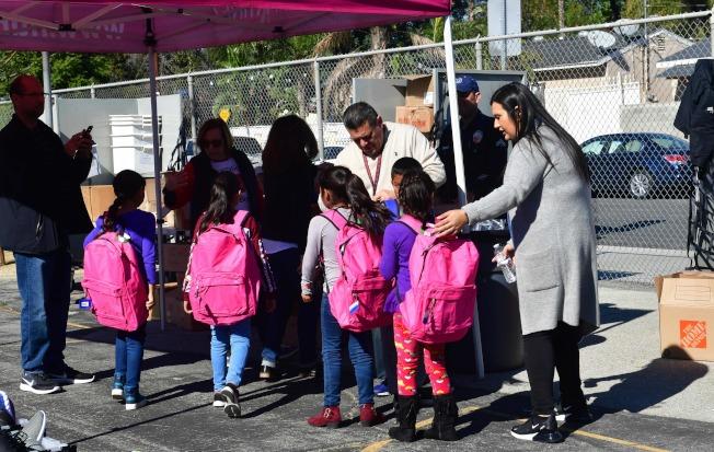 川普為打擊無證移民,曾有意阻止他們的子女上學。圖為加州慈善組織在洛杉磯郊區的一所小學外面為貧窮的移民子女提供書包等免費學用品。(Getty Images)