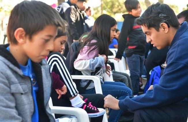 川普為打擊無證移民,有意阻止他們的子女上學。圖為加州慈善組織在洛杉磯郊區的一所小學外面為貧窮的移民子女提供衣服鞋子等免費學用品。(Getty Images)