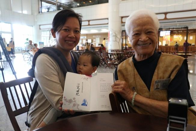 周小姐(左)因媽媽喜歡蔡寬(右),特地抱著女兒到簽書會合影。(圖:台中慈濟醫院提供)