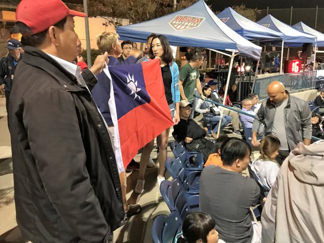 中華隊赴美國加州爾灣參加U19世界盃女壘賽,熱情僑胞拿出大面國旗,遭到大會制止。一名美國籍的台灣女婿(右)與大會人員爭執,遭趕出球場。(中央社)