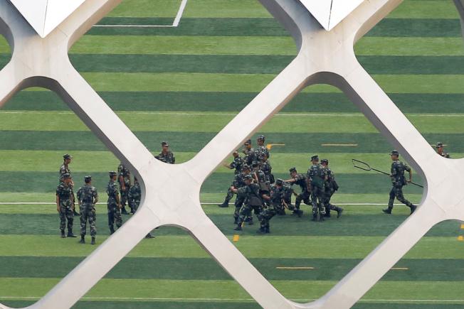 中國在毗鄰香港的深圳灣集結大批武警,準備因應香港局勢。圖為武警在深圳灣體育中心進行鎮暴訓練。(路透)
