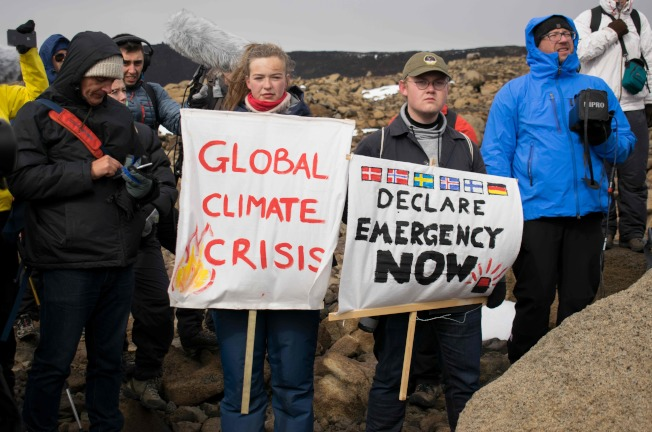參加冰山追悼會的冰島民眾18日手持「氣候變遷危機」等標語,呼籲正視氣候變遷的嚴重。(Gety Images)