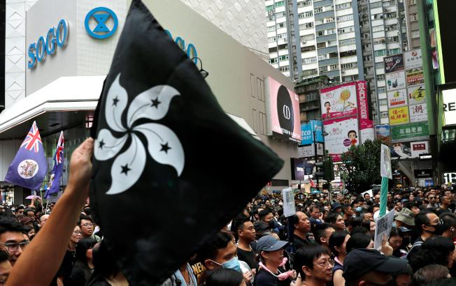 數以萬計的香港民眾18日冒雨撐傘上街在維園自動集結示威,要求港府啟動真民的普選。(路透)
