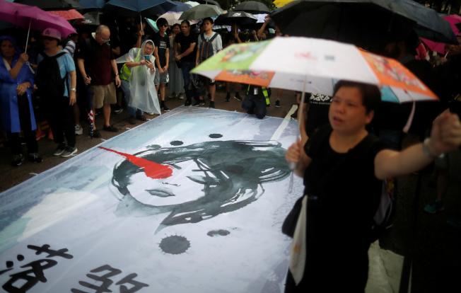 反送中示威者手持雨傘,不畏大雨走向街頭,要求港府回應五大訴求。(路透)