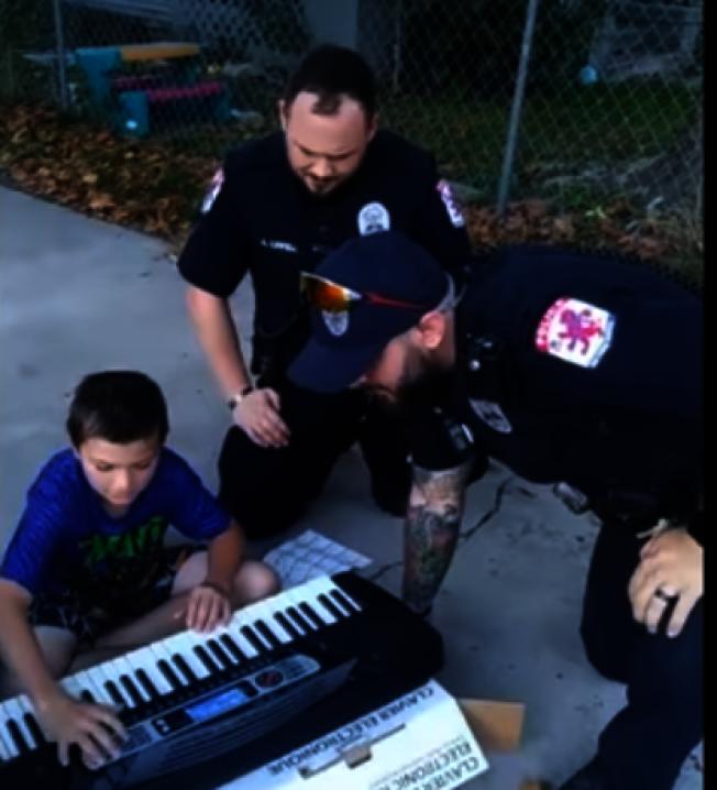 灣城警員帕金斯(戴帽者)在前往協助報案民眾的過程中得知小男孩魯尼喜愛音樂,事後特地帶了新電子琴當禮物。(取自灣城警局臉書)