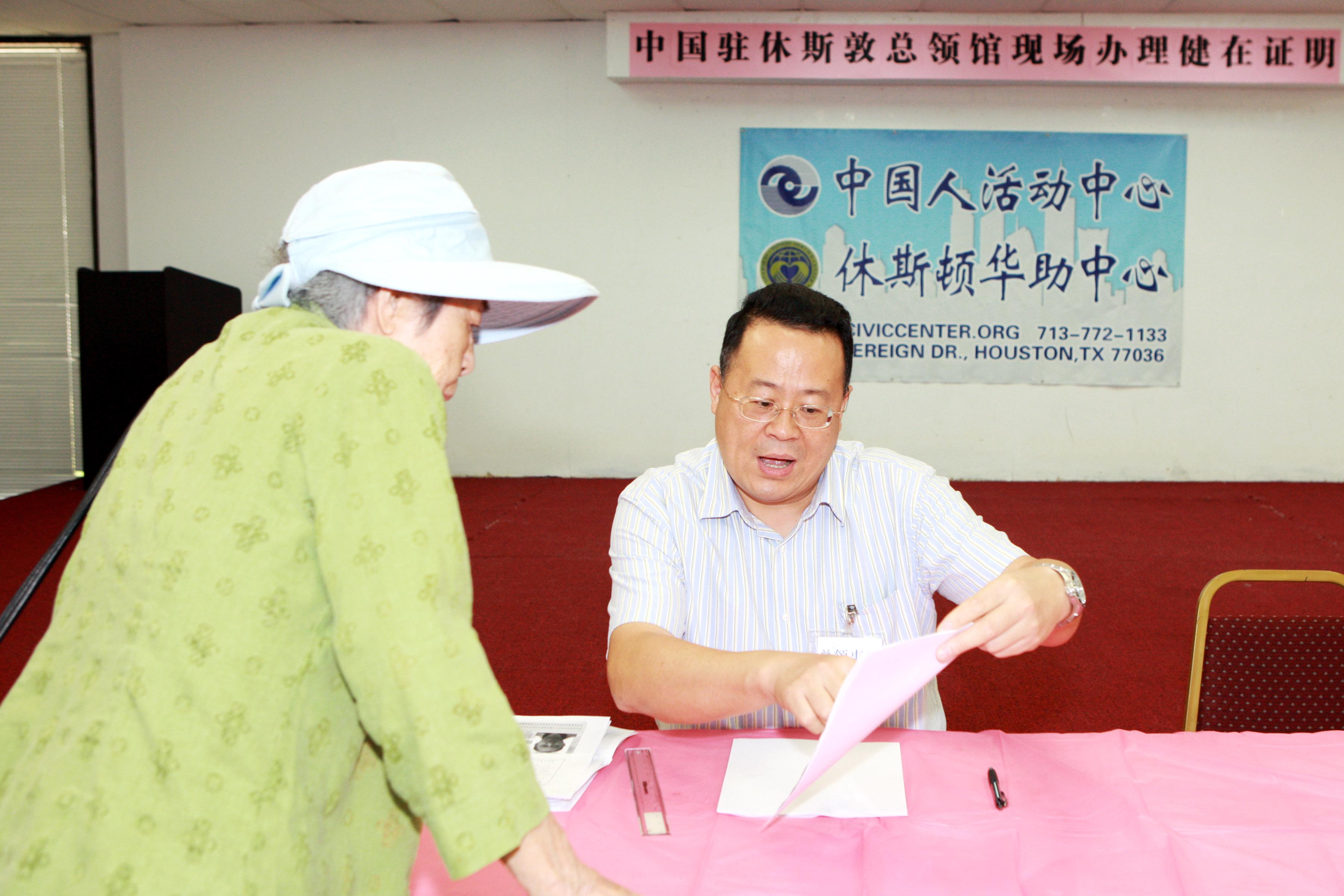 中領館證件處領事向辦證老人詳解相關辦證要求。(記者賈忠/攝影)