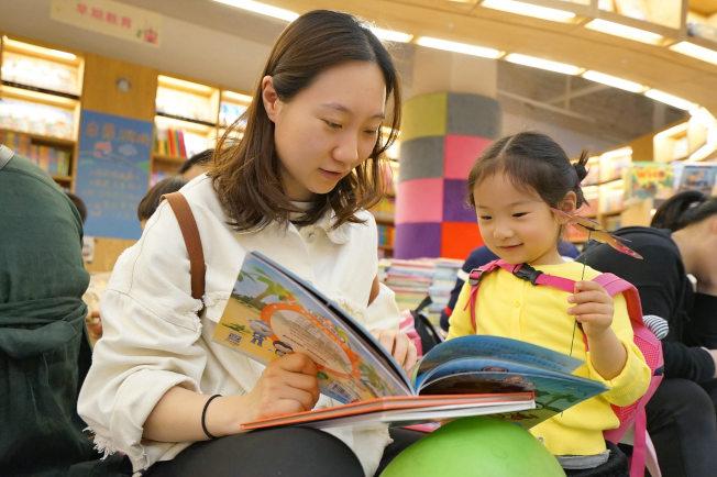親子一起閱讀,能培養孩子的閱讀興趣。(新華社)