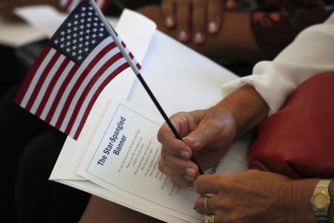 人口普查局最新資料顯示,移民入籍後,與本土出生者的經濟差距縮小。圖為一名婦女上周在佛州里達州一場入籍儀式上手執國旗等候宣誓。(美聯社)