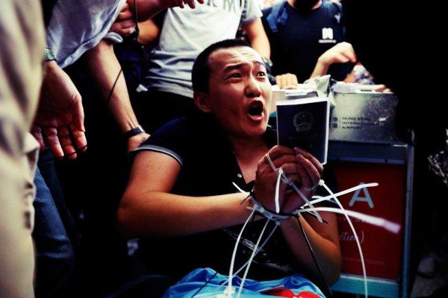 環球時報記者付國豪,被示威者綑綁。 (路透)