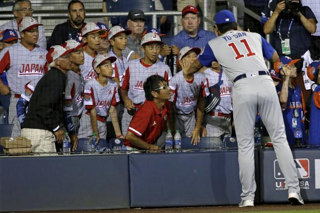 達比修(左)和日本代表隊的小選手們講話。(美聯社)