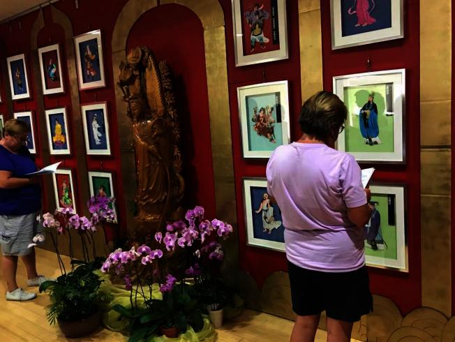 大悲咒觀音菩薩84尊化身立體紙雕,「大悲心陀羅尼經紙雕特展」,訪客持中英文小冊賞析圖像。(佛光會提供)。