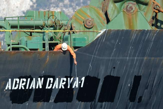 遭英屬直布羅陀扣押的伊朗油輪18日駛離直布羅陀。圖為船員查看油輪新名字「阿德里安.達爾亞一號」。(Getty Images)
