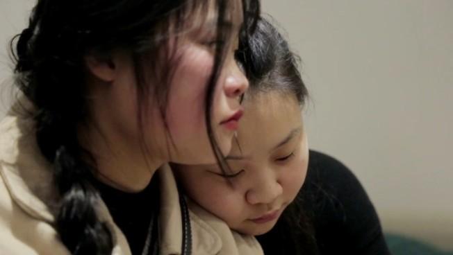 短短幾天相聚已經姊妹情深,曾芳芳(右)低頭靠在妹妹肩上。(洛杉磯時報)