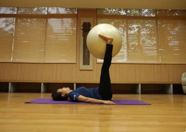 躺姿,兩踝夾緊瑜伽球往上高舉。(圖:蔡娟秀提供)