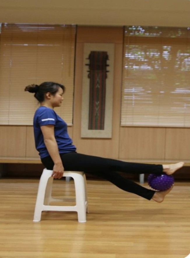 坐姿,兩踝夾緊瑜伽球平舉。(圖:蔡娟秀提供)
