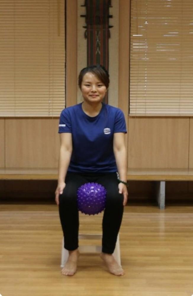 坐姿,兩腿內側夾緊瑜伽球。(圖:蔡娟秀提供)