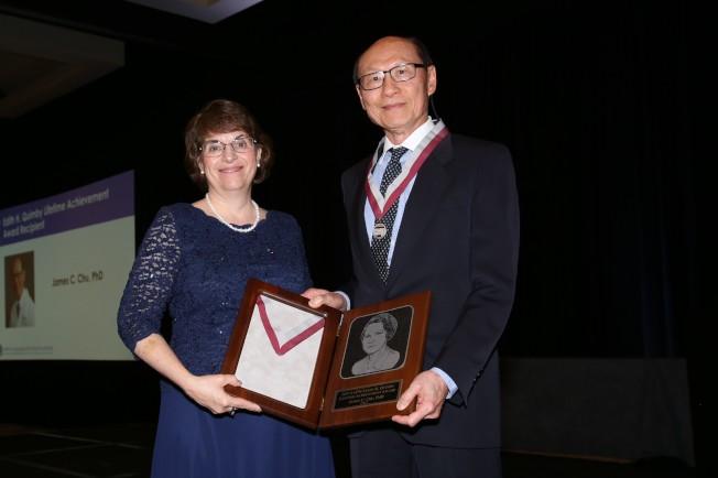 美國醫藥物理學會會長麥克勞(Cynthia H. McCollough,左)頒獎給朱建華(右)。(朱建華提供)