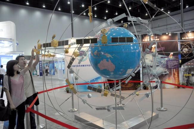 北斗衛星導航系統是中國自行研製的全球衛星導航系統。圖為觀眾在上海參觀北斗衛星導航系統組網模型示意圖。(中新社資料照)